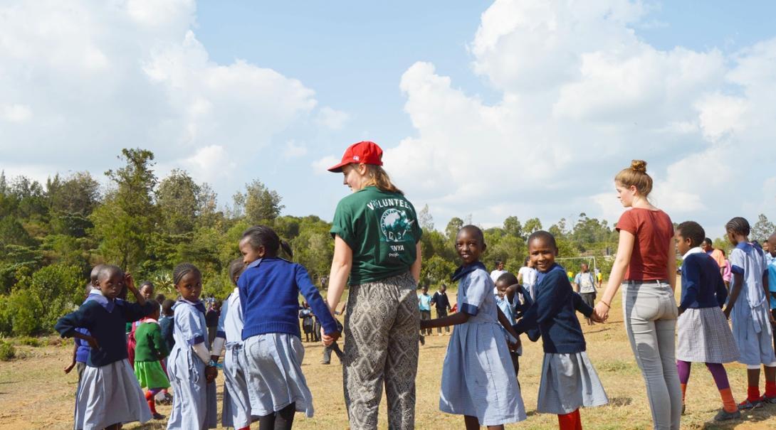 校庭で元気よく遊ぶケニアの子供たちと高校生ボランティア